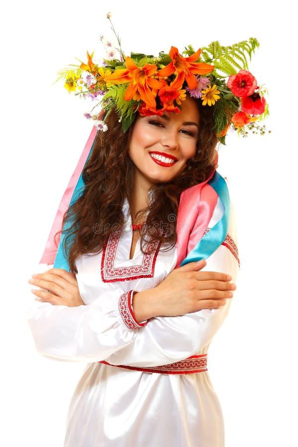 Όμορφη ουκρανική νέα γυναίκα στη γιρλάντα των θερινών λουλουδιών και στοκ φωτογραφία με δικαίωμα ελεύθερης χρήσης