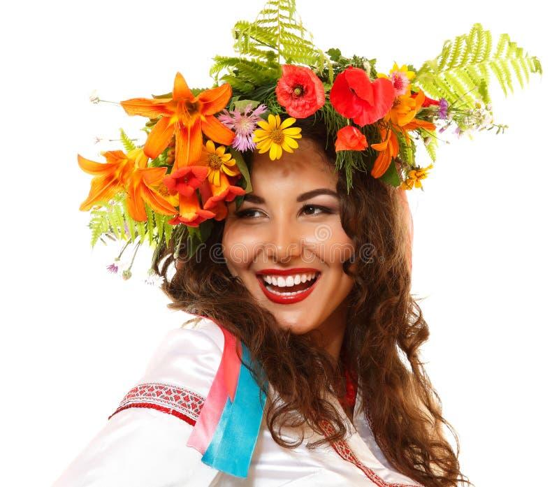 Όμορφη ουκρανική νέα γυναίκα στη γιρλάντα των θερινών λουλουδιών και στοκ εικόνα με δικαίωμα ελεύθερης χρήσης
