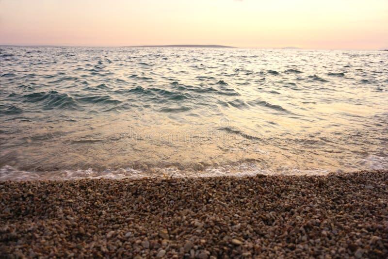 Όμορφη παλίρροια ακτών και θάλασσας σε μια παραλία χαλικιών στο ηλιοβασίλεμα στοκ εικόνες