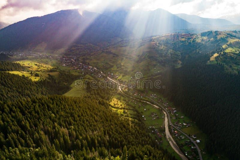 Όμορφη πανοραμική άποψη από τον αέρα στα Καρπάθια βουνά με τα σύννεφα και τις ακτίνες ήλιων στο πρώτο πλάνο στοκ εικόνα