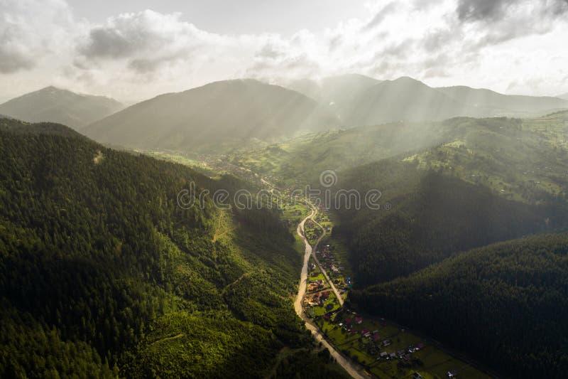 Όμορφη πανοραμική άποψη από τον αέρα στην κοιλάδα με το χωριό στα Καρπάθια βουνά με τα σύννεφα και τις ακτίνες ήλιων μέσα στοκ φωτογραφίες