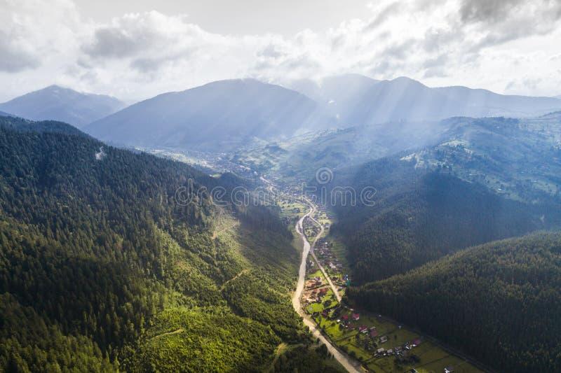 Όμορφη πανοραμική άποψη από τον αέρα στην κοιλάδα με το χωριό στα Καρπάθια βουνά με τα σύννεφα και τις ακτίνες ήλιων μέσα στοκ φωτογραφία