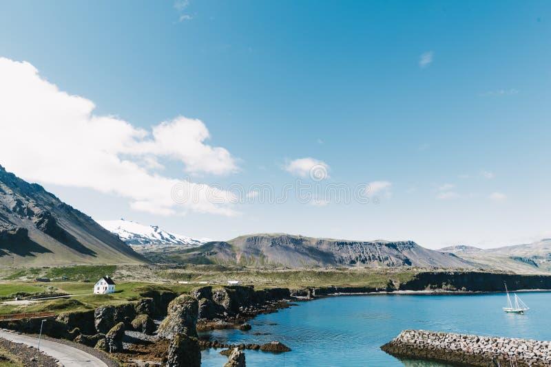 όμορφη παραλία με το επιπλέον γιοτ στο νερό, το δρόμο, τα δύσκολα βουνά και τα σπίτια στην ακτή στο gatklettur, arnarstapi, Ισλαν στοκ φωτογραφίες