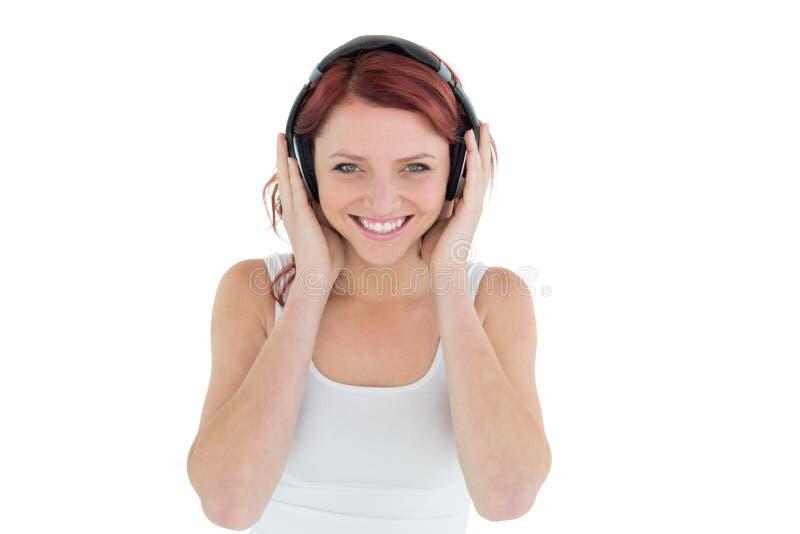 Όμορφη περιστασιακή γυναίκα που απολαμβάνει τη μουσική μέσω των ακουστικών στοκ εικόνες με δικαίωμα ελεύθερης χρήσης