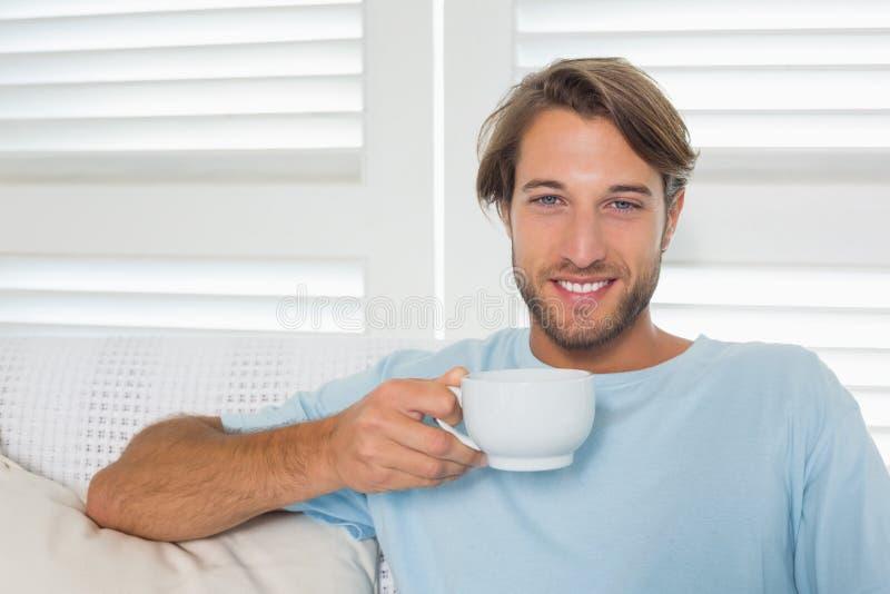 Όμορφη περιστασιακή συνεδρίαση ατόμων στον καναπέ που έχει τον καφέ στοκ εικόνες