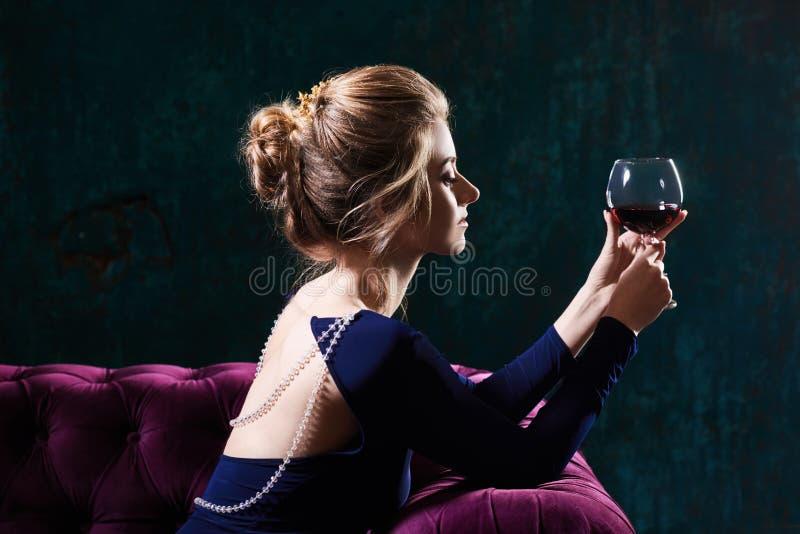 Όμορφη πολυτελής ξανθή συνεδρίαση γυναικών σε έναν εκλεκτής ποιότητας καναπέ δέρματος με το ποτήρι του κόκκινου κρασιού στοκ εικόνες με δικαίωμα ελεύθερης χρήσης