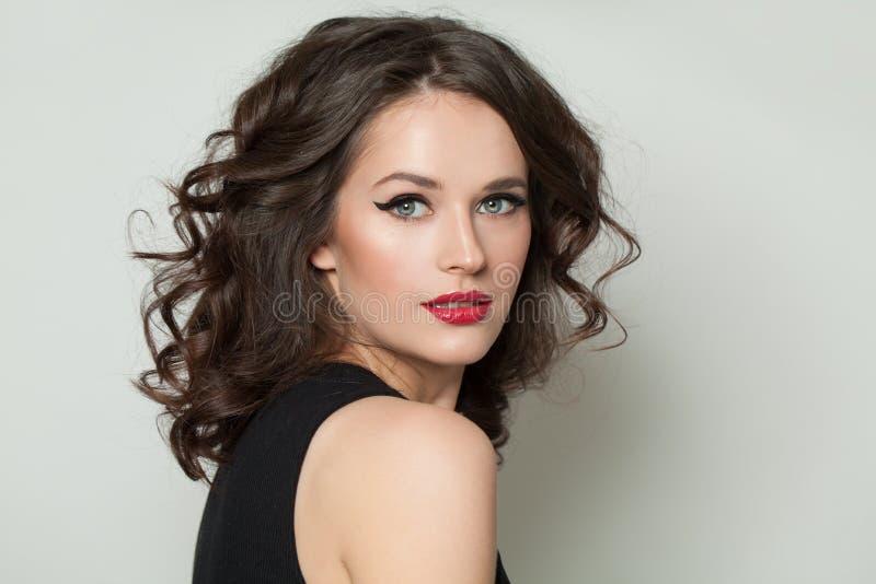 Όμορφη προκλητική γυναίκα που εξετάζει τη κάμερα Όμορφο πρότυπο με το makeup και το καφετί σγουρό πορτρέτο τρίχας στοκ εικόνες