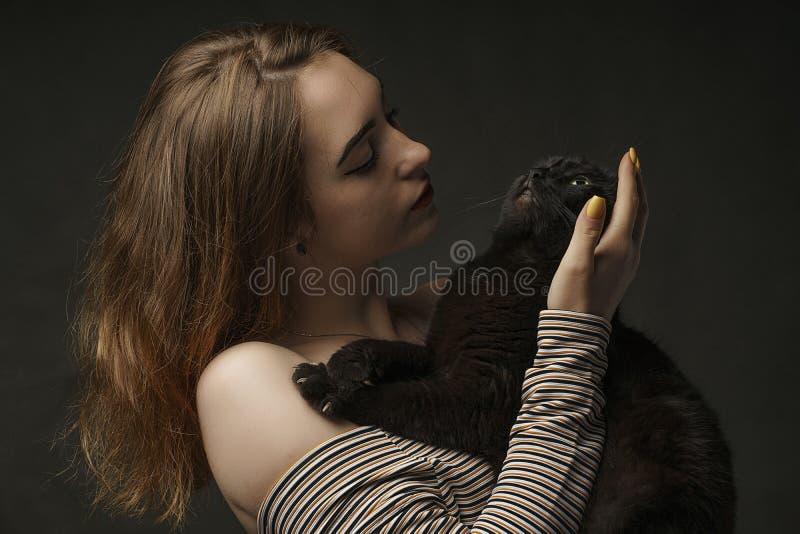 Όμορφη προκλητική γυναίκα στη μαύρη μαύρη γάτα εκμετάλλευσης Όμορφη νέα και μοντέρνη γυναίκα που κρατά μια γκρίζα γάτα Φωτογραφία στοκ εικόνες