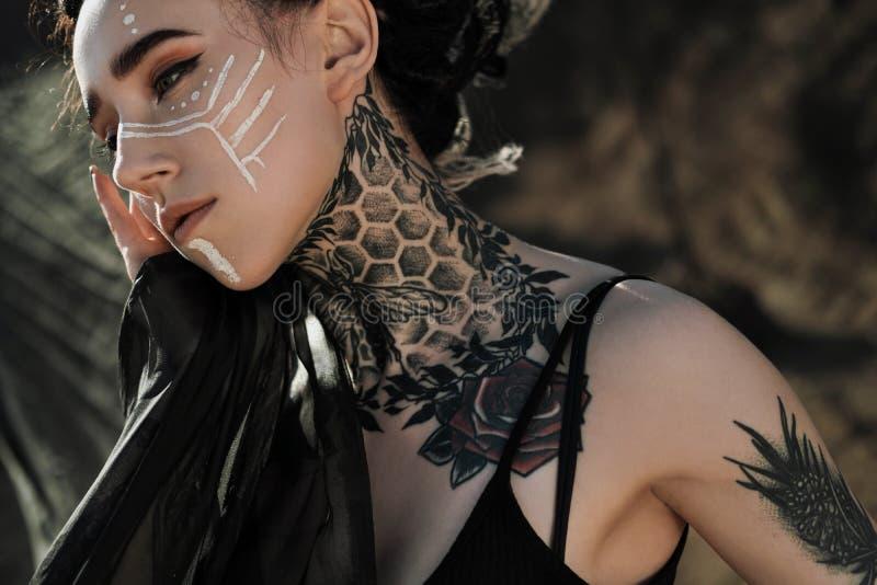 Όμορφη προκλητική γυναίκα στο μαύρο εσώρουχο Το σώμα καλύπτεται με πολλές δερματοστιξίες Dreadlocks στο κεφάλι Τοποθέτηση ενάντια στοκ φωτογραφία