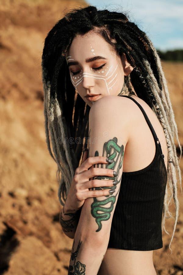 Όμορφη προκλητική γυναίκα στο μαύρο εσώρουχο Το σώμα καλύπτεται με πολλές δερματοστιξίες Dreadlocks στο κεφάλι Τοποθέτηση ενάντια στοκ εικόνες