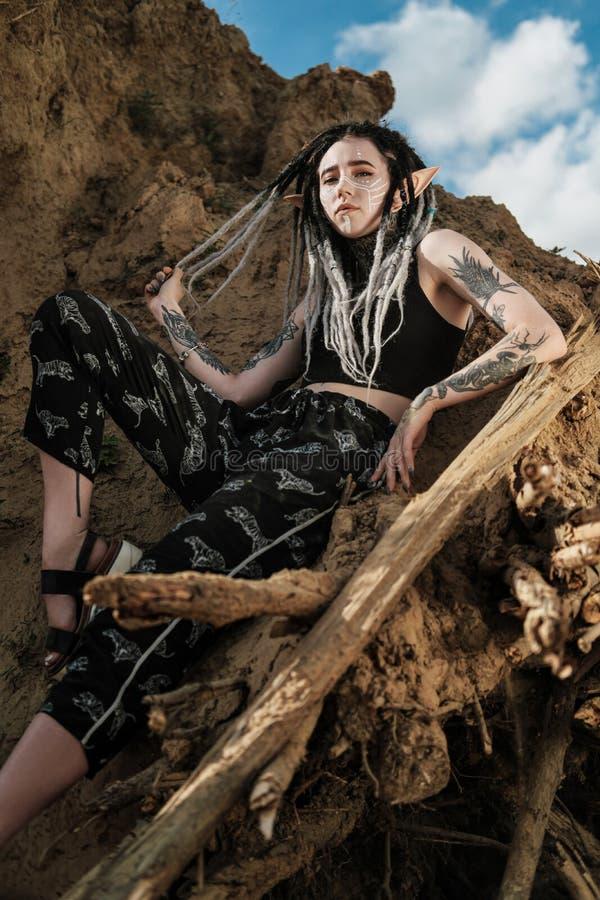 Όμορφη προκλητική γυναίκα στο μαύρο εσώρουχο Το σώμα καλύπτεται με πολλές δερματοστιξίες Dreadlocks στο κεφάλι Τοποθέτηση ενάντια στοκ φωτογραφία με δικαίωμα ελεύθερης χρήσης
