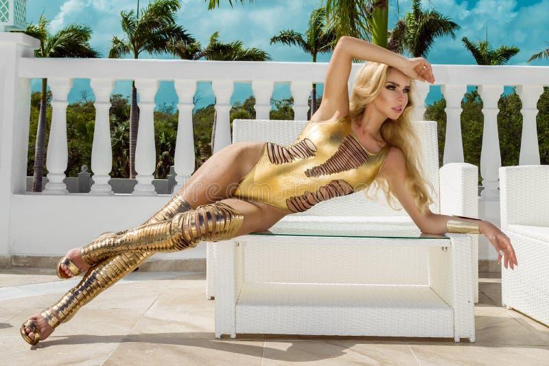 Όμορφη προκλητική γυναίκα στο χρυσό μπικίνι και τα χρυσά παπούτσια που θέτουν στο καραϊβικό ξενοδοχείο πολυτελείας στοκ εικόνα