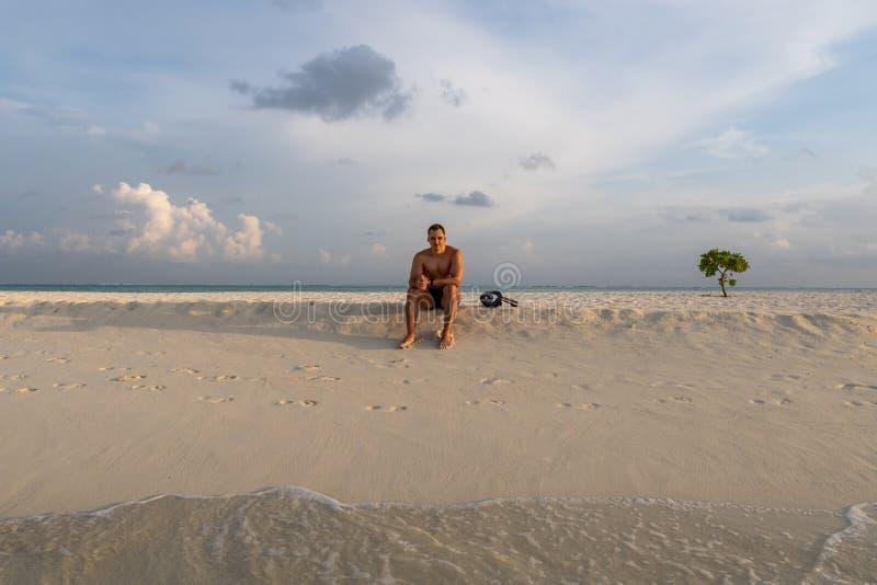Όμορφη προκλητική τόπλες αρσενική χαλαρωμένη πρότυπο συνεδρίαση στην παραλία στοκ εικόνες