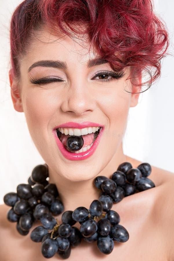 Όμορφη προκλητική redhead γυναίκα με ένα μαύρο σταφύλι μεταξύ του Teet της στοκ φωτογραφία με δικαίωμα ελεύθερης χρήσης