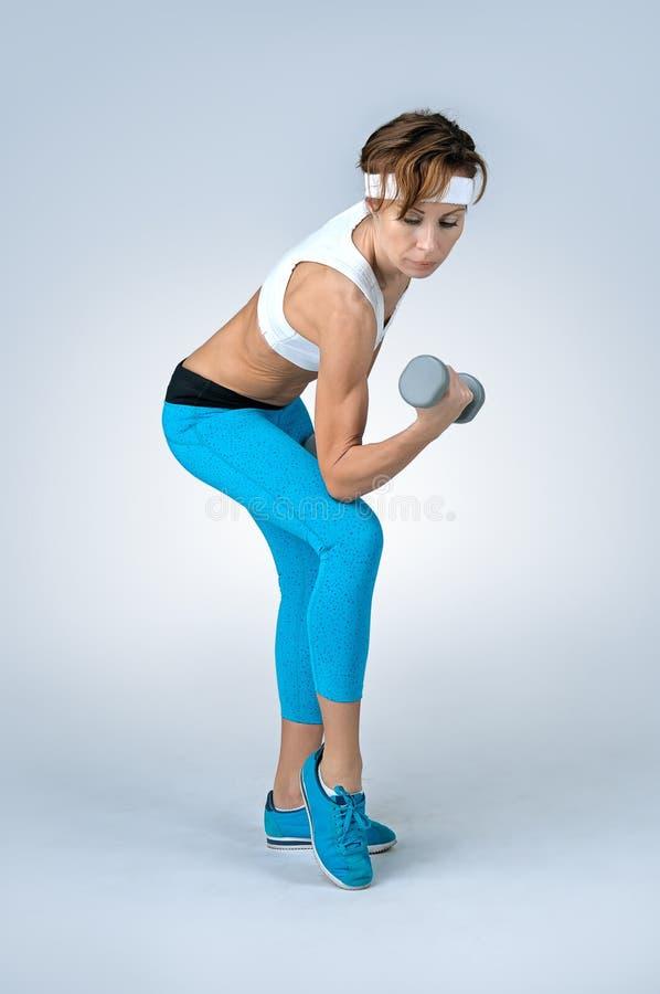 Όμορφη προκλητική γυναίκα αθλητικής ικανότητας που κάνει workout την άσκηση με το δ στοκ φωτογραφία