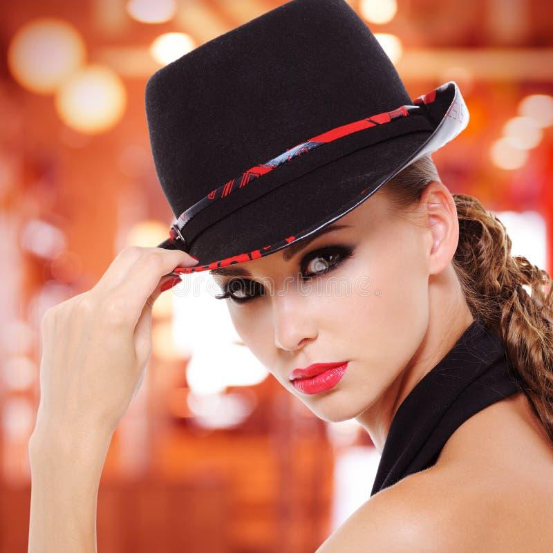 Όμορφη προκλητική γυναίκα με τα κόκκινα χείλια και το μαύρο καπέλο στοκ εικόνες