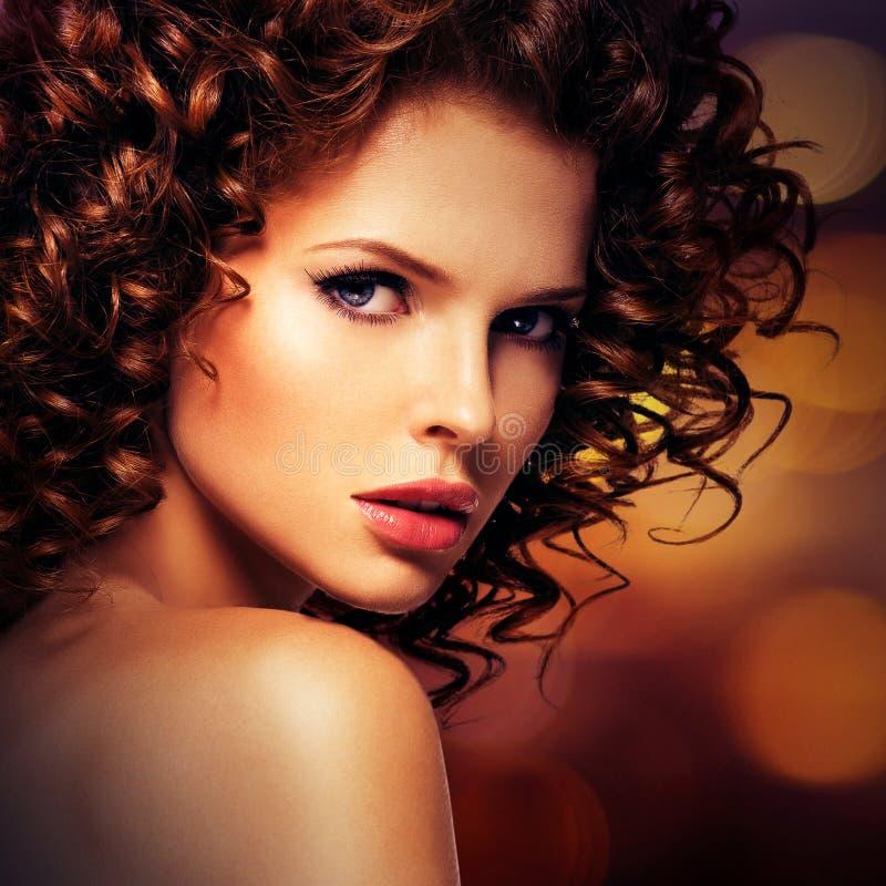 Όμορφη προκλητική γυναίκα με τη σγουρή τρίχα brunette στοκ φωτογραφία