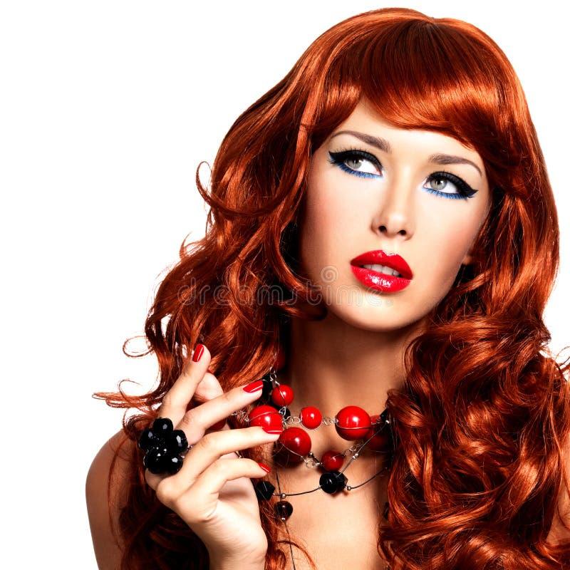Όμορφη προκλητική γυναίκα με τις μακριές κόκκινες τρίχες και τα φωτεινά κόκκινα χείλια. στοκ φωτογραφία