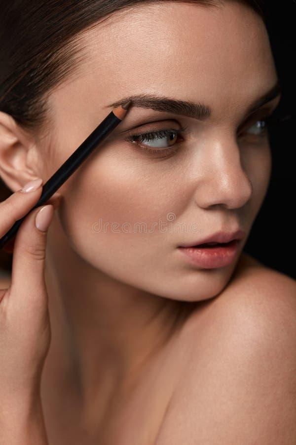 Όμορφη προκλητική γυναίκα που περιγράφει τα φρύδια γοητευτικό makeup στοκ εικόνες με δικαίωμα ελεύθερης χρήσης