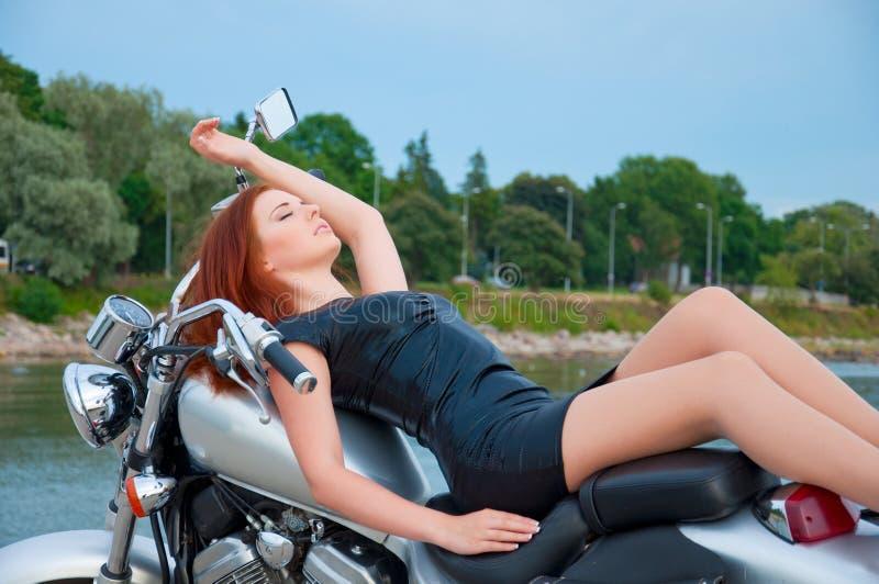 Όμορφη, προκλητική, νέα γυναίκα σε μια μοτοσικλέτα στοκ φωτογραφίες με δικαίωμα ελεύθερης χρήσης
