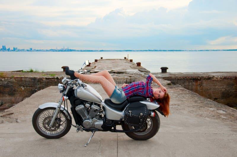 Όμορφη, προκλητική, νέα γυναίκα σε μια μοτοσικλέτα στοκ φωτογραφία