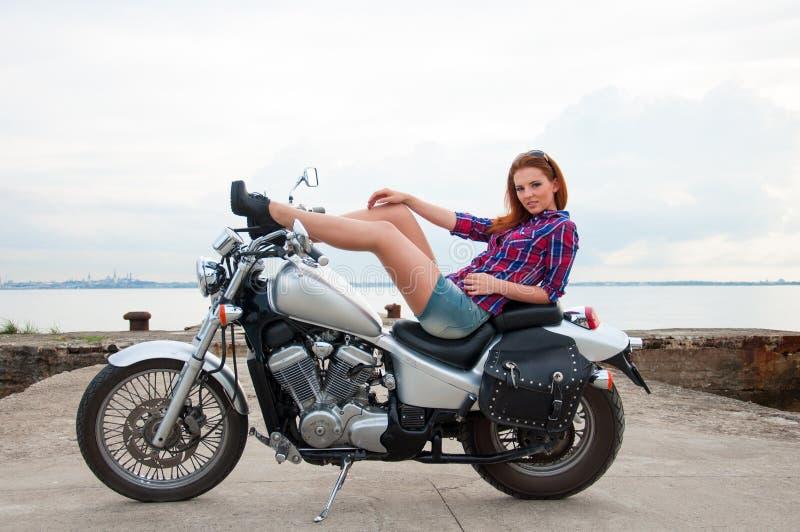 Όμορφη, προκλητική, νέα γυναίκα σε μια μοτοσικλέτα στοκ εικόνα