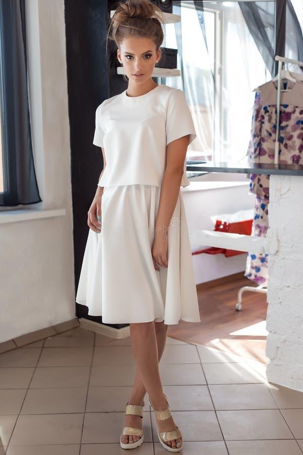 Όμορφη προκλητική νέα γυναίκα στο όμορφο μοντέρνο άσπρο φόρεμα στην τοποθέτηση στούντιο για το βλαστό μόδας καμερών για τον ιματι στοκ εικόνες