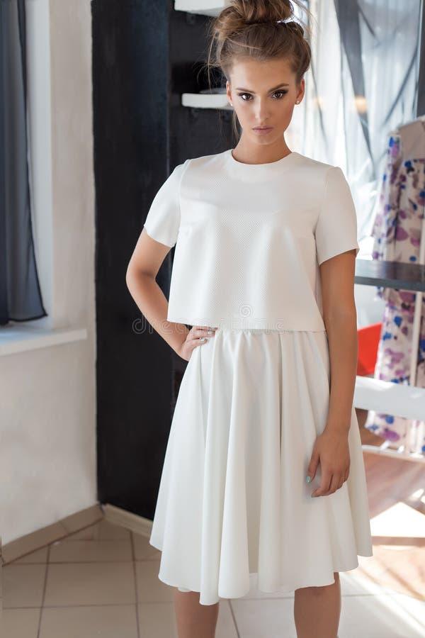 Όμορφη προκλητική νέα γυναίκα στο όμορφο μοντέρνο άσπρο φόρεμα στην τοποθέτηση στούντιο για το βλαστό μόδας καμερών για τον ιματι στοκ εικόνα με δικαίωμα ελεύθερης χρήσης