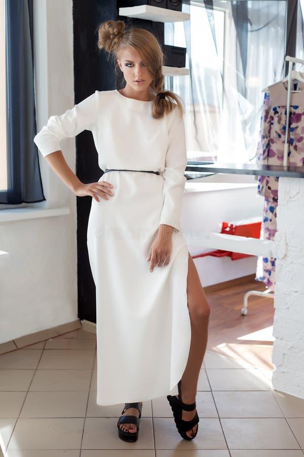 Όμορφη προκλητική νέα γυναίκα στο όμορφο μοντέρνο άσπρο φόρεμα στην τοποθέτηση στούντιο για το βλαστό μόδας καμερών για τον ιματι στοκ φωτογραφία με δικαίωμα ελεύθερης χρήσης