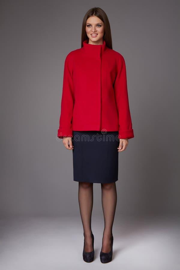 Όμορφη προκλητική νέα επιχειρησιακή γυναίκα με τη σύνθεση βραδιού που φορά μια σκοτεινή φούστα στο γονάτων μαλλιού κόκκινο παλτών στοκ φωτογραφία