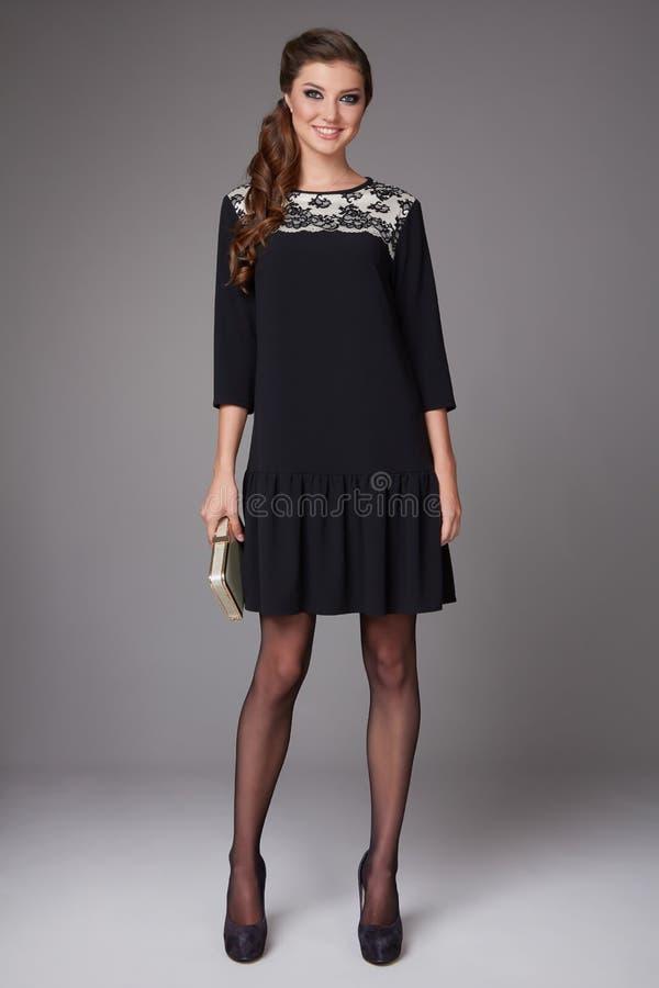 Όμορφη προκλητική νέα επιχειρησιακή γυναίκα με τη σύνθεση βραδιού που φορά ένα φόρεμα και ψηλοτάκουνα παπούτσια και μια μικρή μαύ στοκ φωτογραφία με δικαίωμα ελεύθερης χρήσης