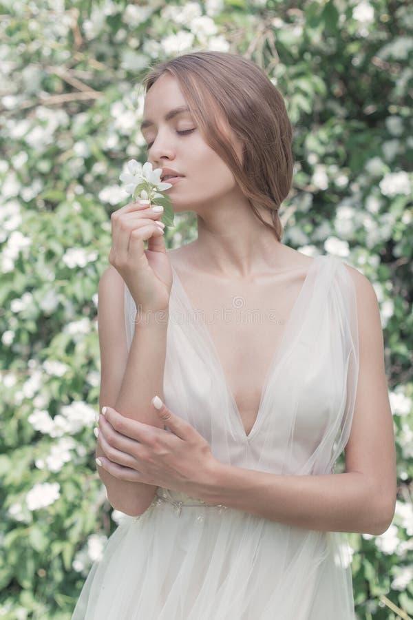 Όμορφη προκλητική νύφη κοριτσιών σε ένα ελαφρύ φόρεμα με τη λεπτή σύνθεση και τρίχα jasmine κήπων λουλουδιών Ορισμένη τέχνη φωτογ στοκ εικόνες με δικαίωμα ελεύθερης χρήσης