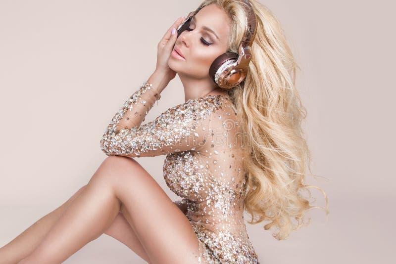 Όμορφη προκλητική ξανθή γυναίκα με το μακρυμάλλες και τέλειο σώμα στο καταπληκτικό φόρεμα με τα χρυσά και ασημένια κρύσταλλα στοκ εικόνες