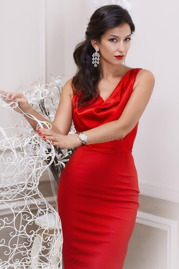 Όμορφη προκλητική πολυτελής καλά-καλλωπισμένη νέα γυναίκα σκουλαρίκια στα κόκκινα κρυψίνους φορεμάτων με μακροχρόνιο μαύρο standi στοκ φωτογραφίες