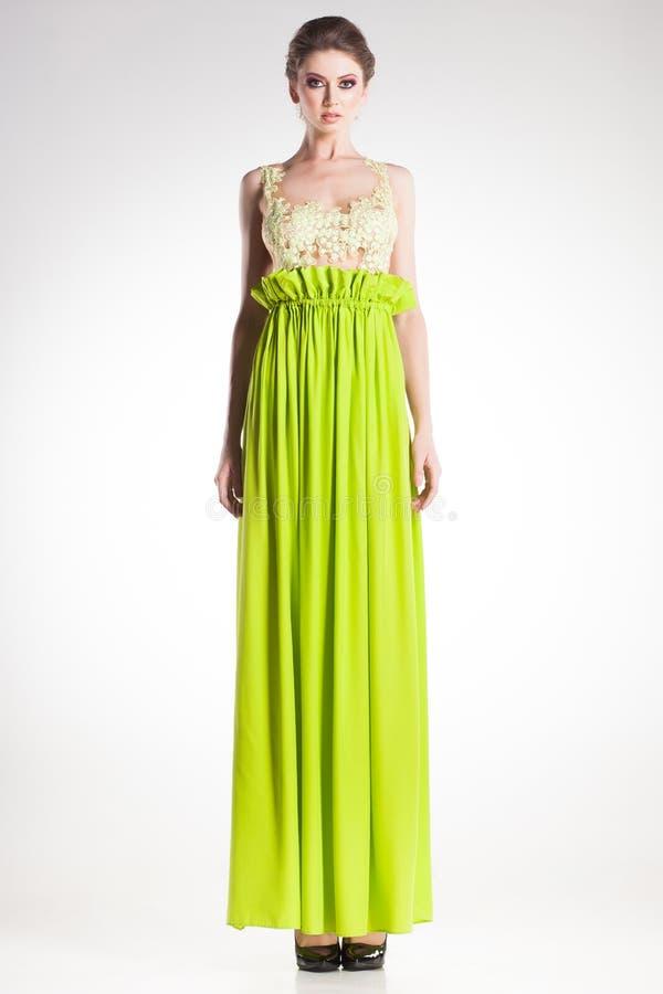 Όμορφη πρότυπη τοποθέτηση γυναικών στο κομψό πράσινο φόρεμα στοκ εικόνες