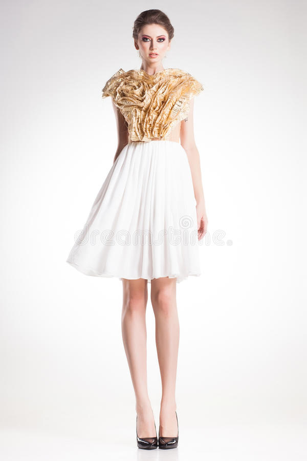 Όμορφη πρότυπη τοποθέτηση γυναικών στο κομψό χρυσό και άσπρο φόρεμα στοκ εικόνα με δικαίωμα ελεύθερης χρήσης