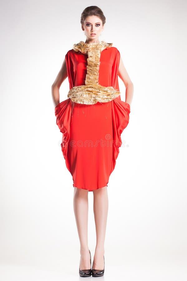 Όμορφη πρότυπη τοποθέτηση γυναικών στο κομψό χρυσό και κόκκινο φόρεμα στοκ φωτογραφία