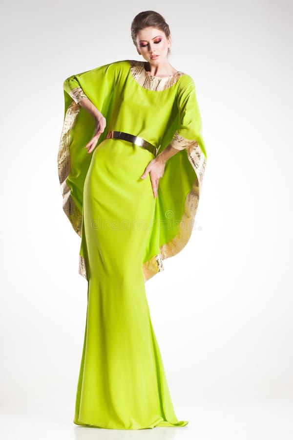 Όμορφη πρότυπη τοποθέτηση γυναικών στο κομψό χρυσό και πράσινο φόρεμα στοκ φωτογραφίες
