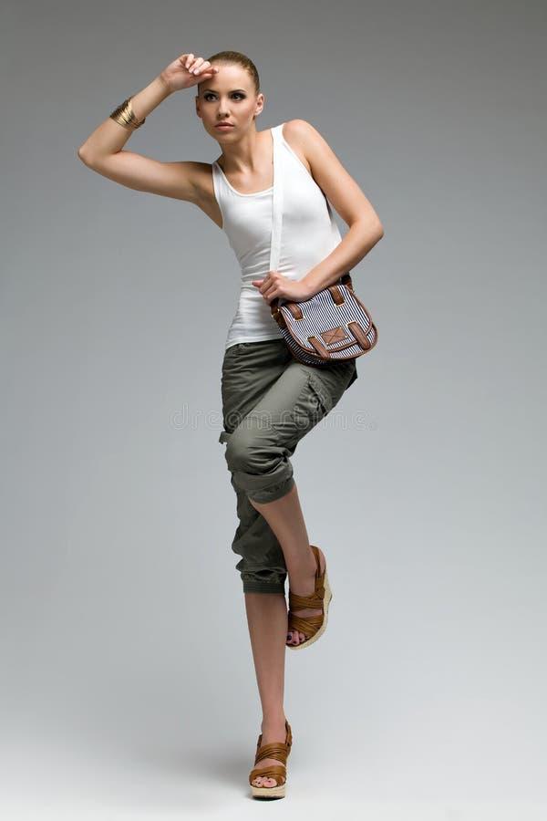 Όμορφη πρότυπη τοποθέτηση μόδας σε ένα πόδι. στοκ εικόνες