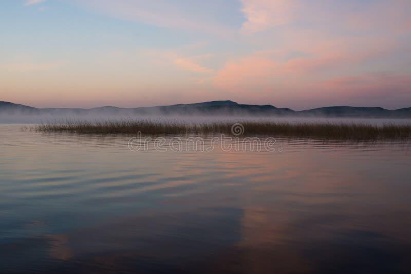 Όμορφη ρόδινη ανατολή της Misty με τις αντανακλάσεις στη μεγάλη λίμνη στοκ φωτογραφία