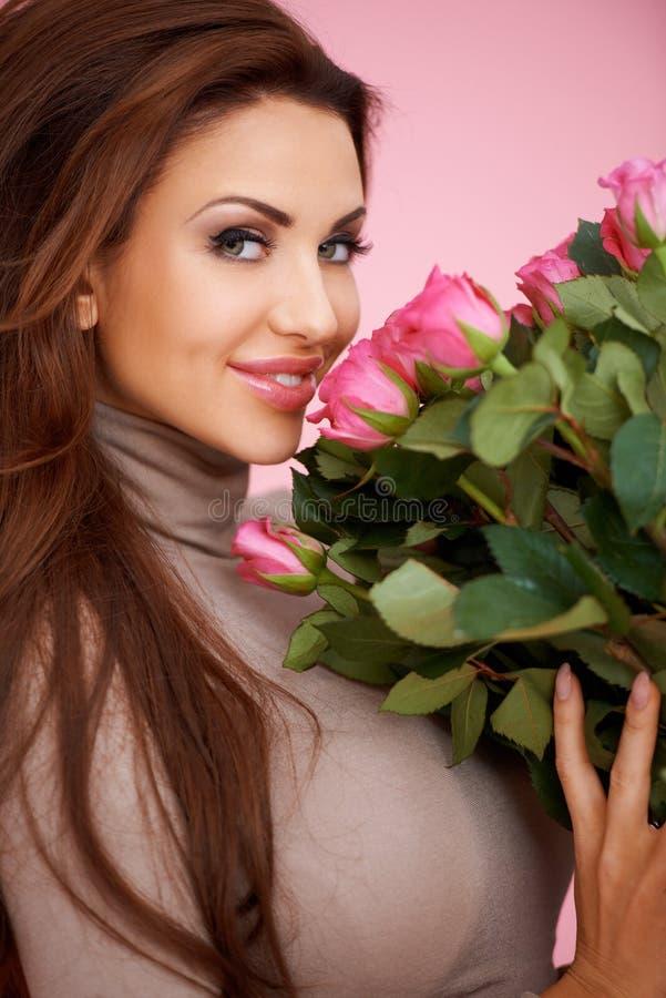 Όμορφη σαγηνευτική γυναίκα με τα τριαντάφυλλα στοκ εικόνες