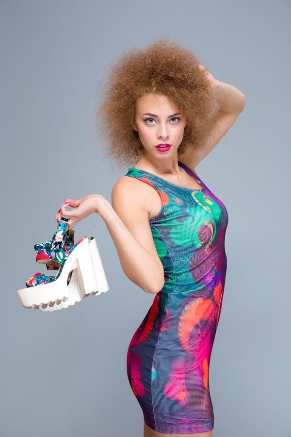 Download Όμορφη σγουρή νέα θηλυκή τοποθέτηση με τα παπούτσια στο χέρι της Στοκ Εικόνες - εικόνα από γοητεία, ζωηρόχρωμος: 62724840