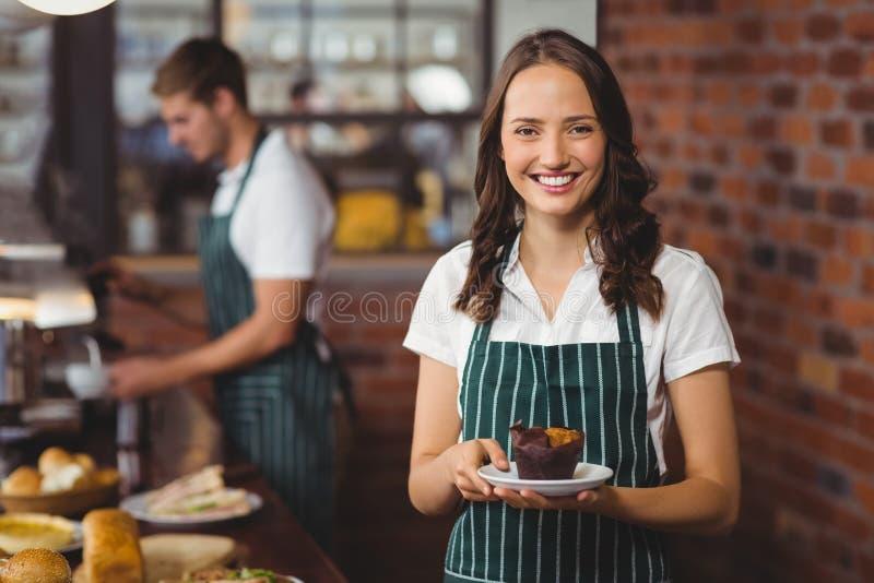 Όμορφη σερβιτόρα που κρατά ένα πιάτο με muffin στοκ φωτογραφία