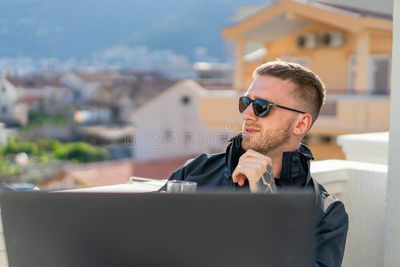 Όμορφη σκεπτική μοντέρνη συνεδρίαση ατόμων στο μπαλκόνι και εργασία στο lap-top στοκ εικόνες