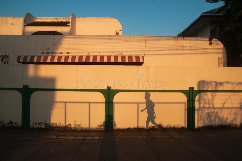 Όμορφη σκιά του δρομέα γυναικών στο υπόβαθρο τοίχων κρέμας Το φως ηλιοβασιλέματος λάμπει κάτω από γύρω από τον τοίχο και το σπίτι στοκ εικόνες
