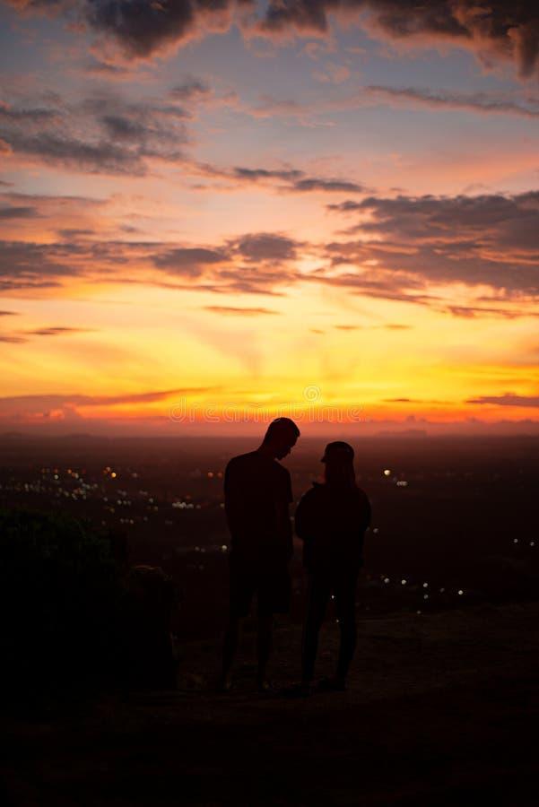 Όμορφη σκιαγραφία ηλιοβασιλέματος του νέου ζεύγους Βουνό το βράδυ στοκ εικόνες