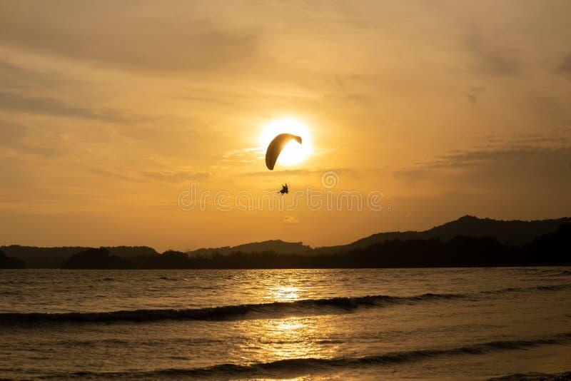 Όμορφη σκιαγραφία του ανεμόπτερου που πετά στον ουρανό του ηλιοβασιλέματος στην παραλία στοκ φωτογραφία