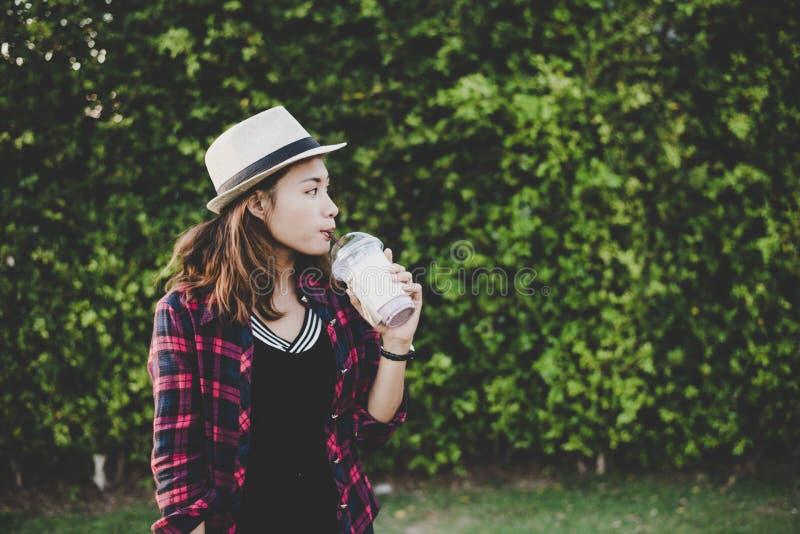 Όμορφη στάση κατανάλωσης γυναικών hipster milkshake κοντά στο πράσινο τ στοκ φωτογραφία με δικαίωμα ελεύθερης χρήσης