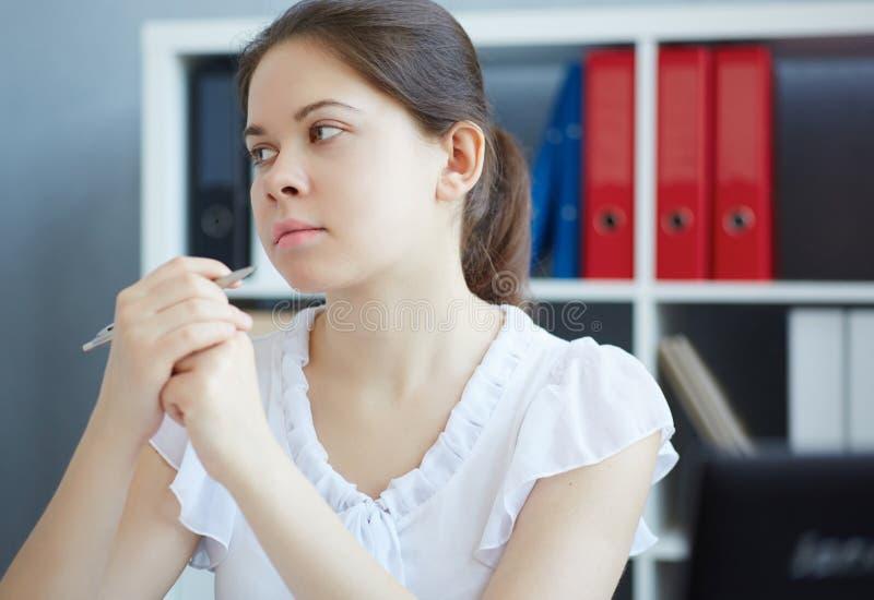 Όμορφη στοχαστική συνεδρίαση γυναικών σπουδαστών ή οικότροφων στον εργασιακό χώρο γραφείων στοκ εικόνες