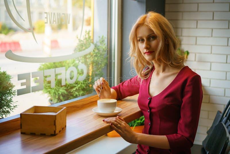 Όμορφη συνεδρίαση γυναικών από το παράθυρο σε έναν καφέ κατανάλωσης καφέδων στοκ φωτογραφίες